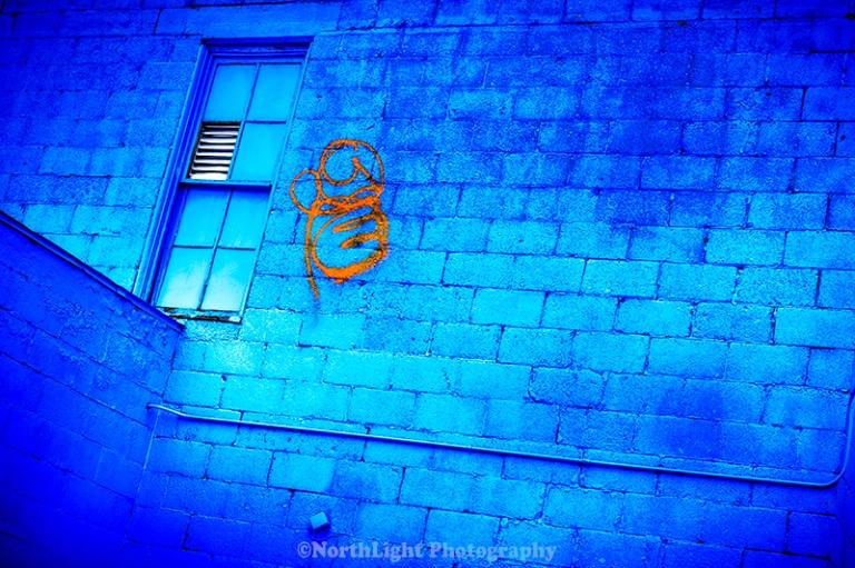 Blue walls, orange graffiti, blue window panes and frames in downtown Ludington, Michigan, USA.