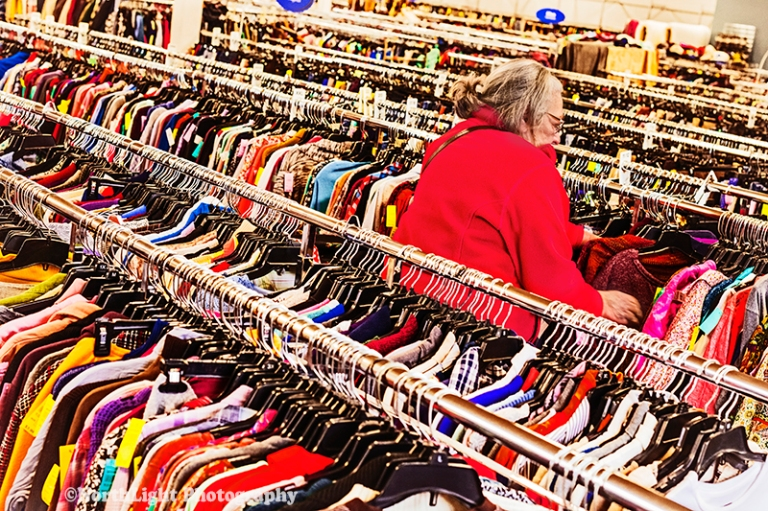 Senior woman in the racks at a thrift shore in Ludington, MI, USA.