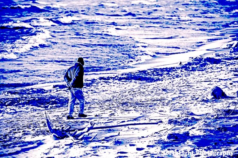 Senior male walking the storm littered beach near the Ludington State Park Beach House in December near Ludington, Michigan, USA