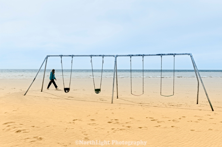 Beachcomber walking past swing set at Douglas Park, First Street Beach on Lake Michigan in the city of Manistee, Michigan, USA.